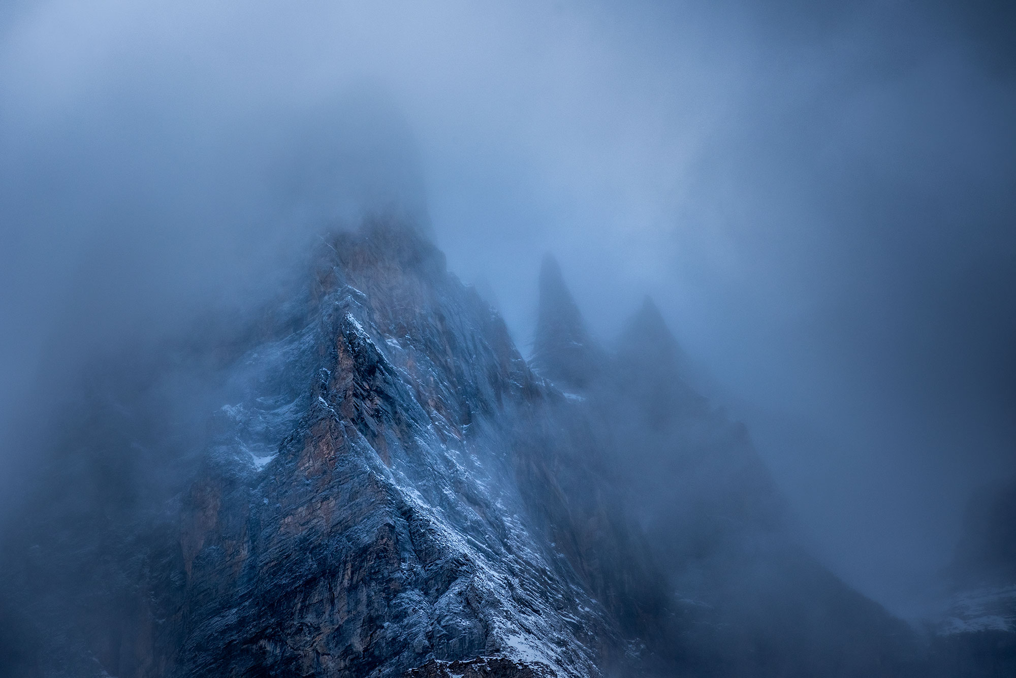 Moody and dramatic landscape photography of the Swiss Alps in the fog. Image by Jennifer Esseiva.