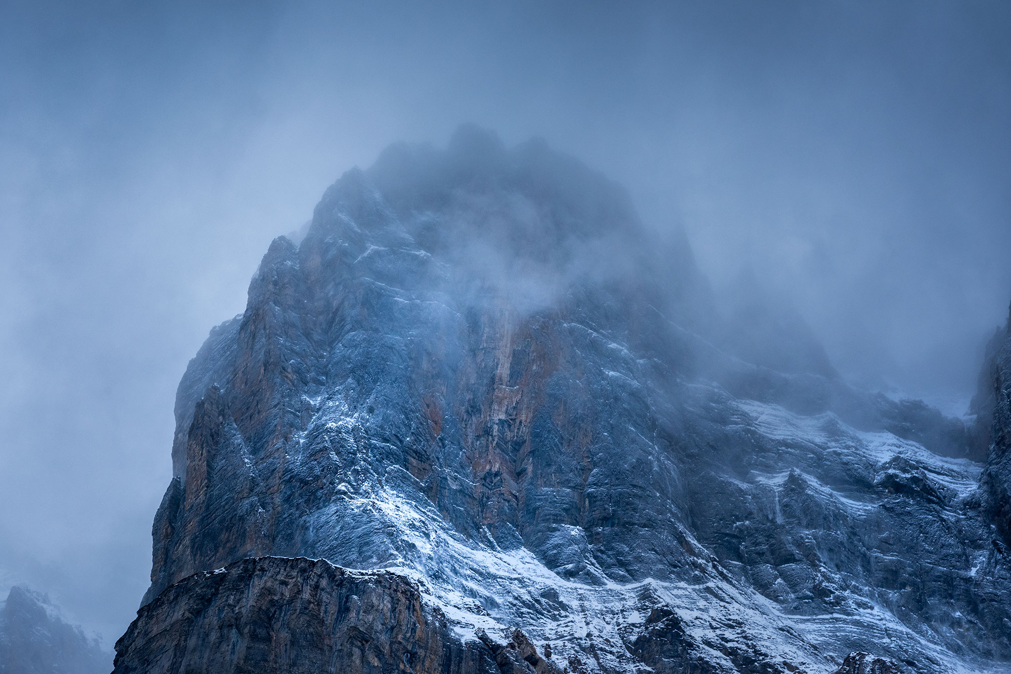 Moody and dramatic landscape photography of the Swiss Alps in the fog.