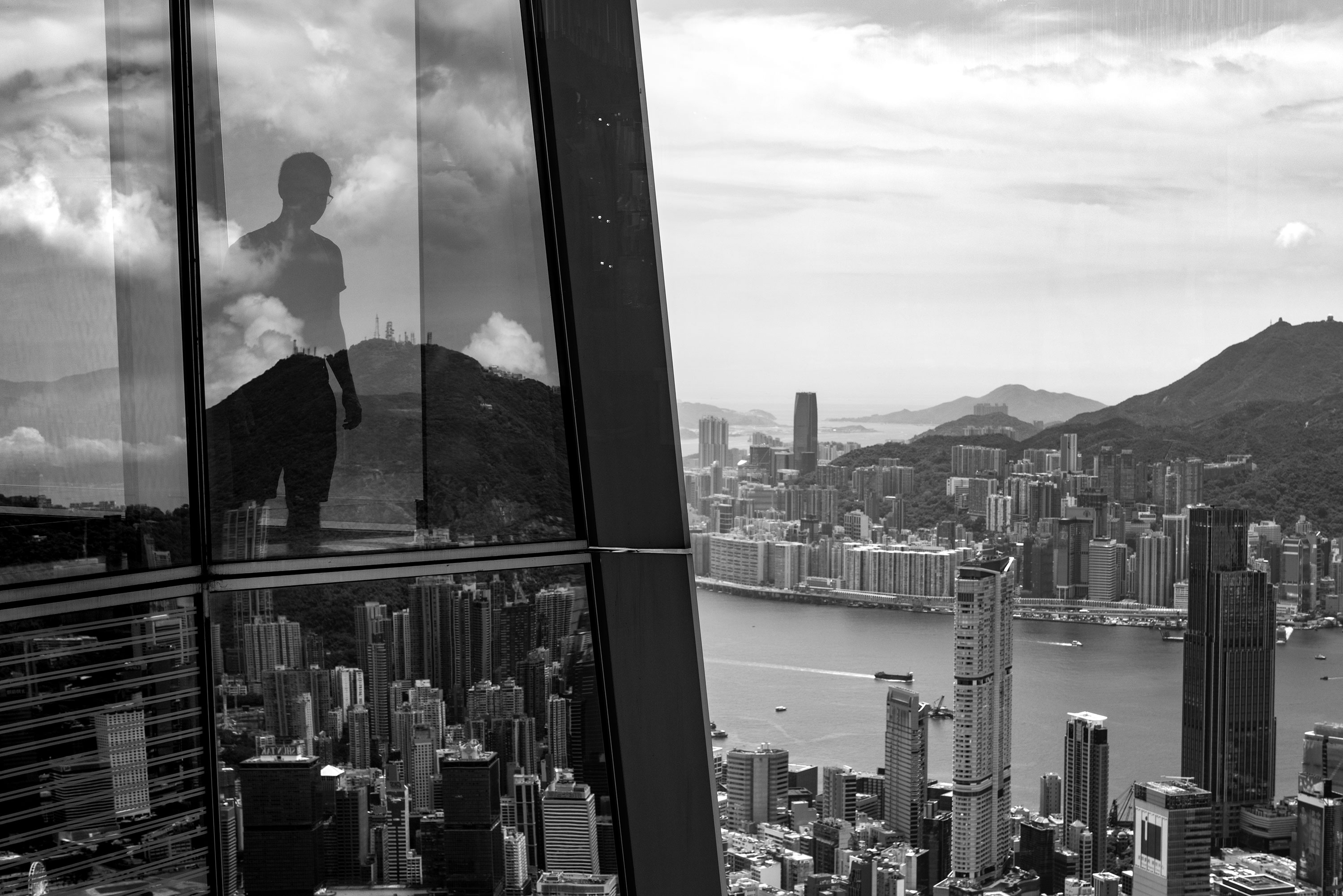 Black and white photography of a person looking down the street from the 100th of the highest tower in Kowloon taken by Jennifer Esseiva.