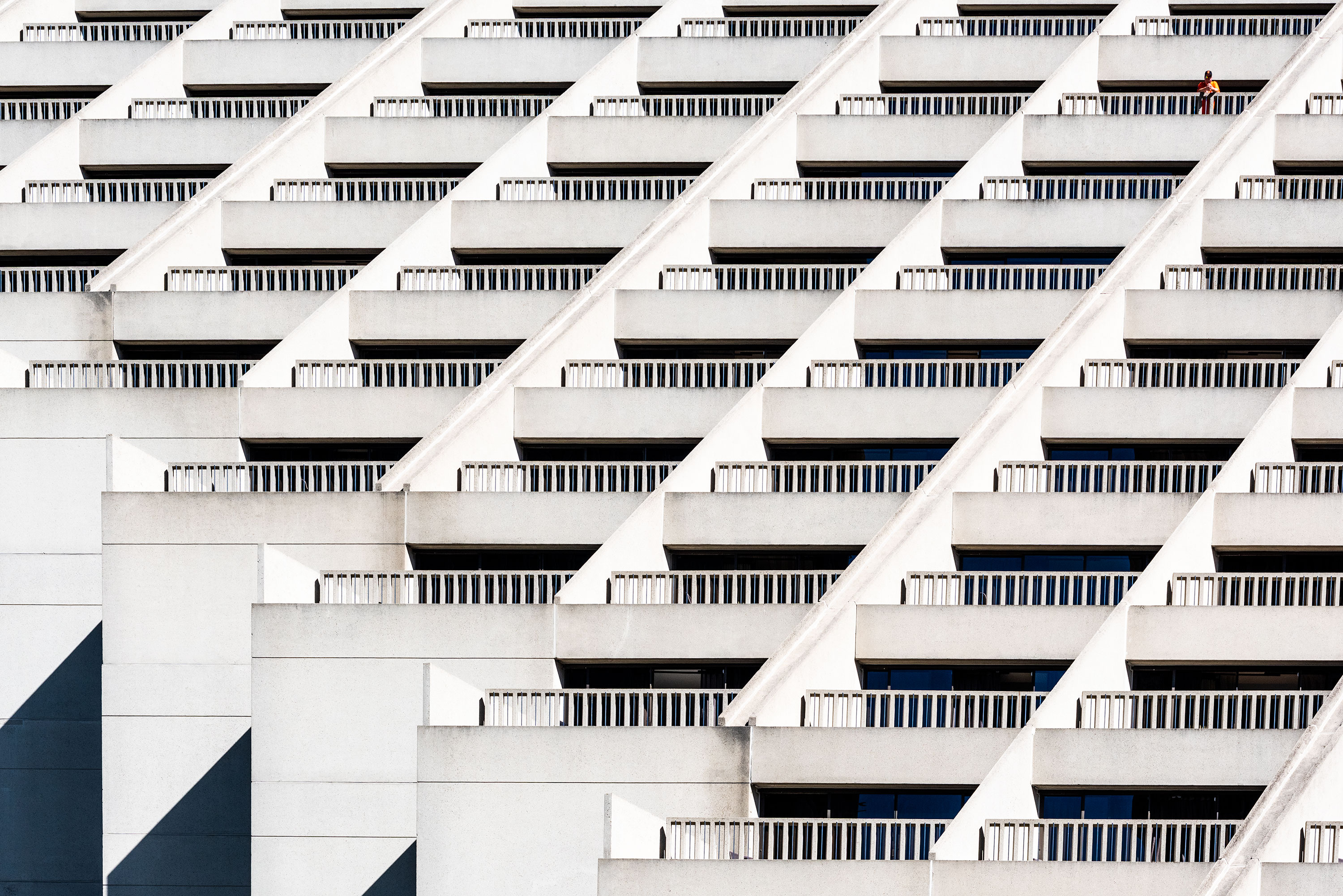 Graphical and close-up photography of a white building in San Fransisco. And man is standing on his balcony, looking down the street.