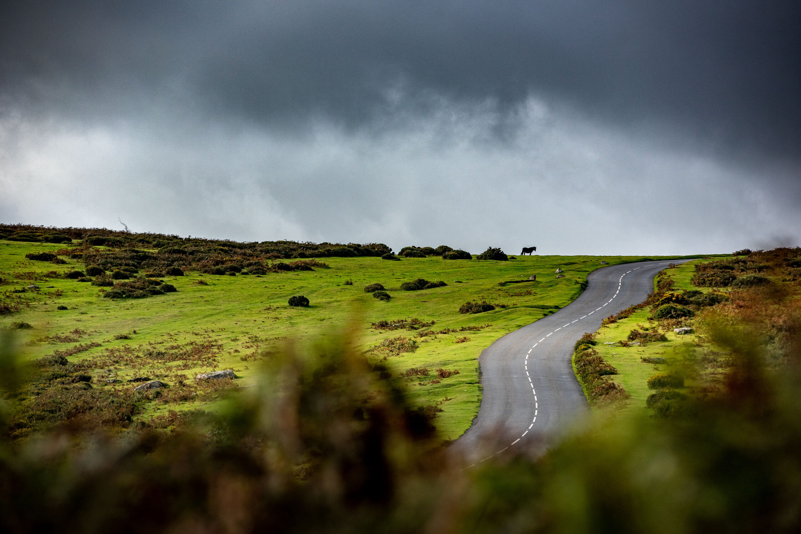 Dramatic and moody photography of a road crossing the Dartmoor. Image by Jennifer Esseiva.