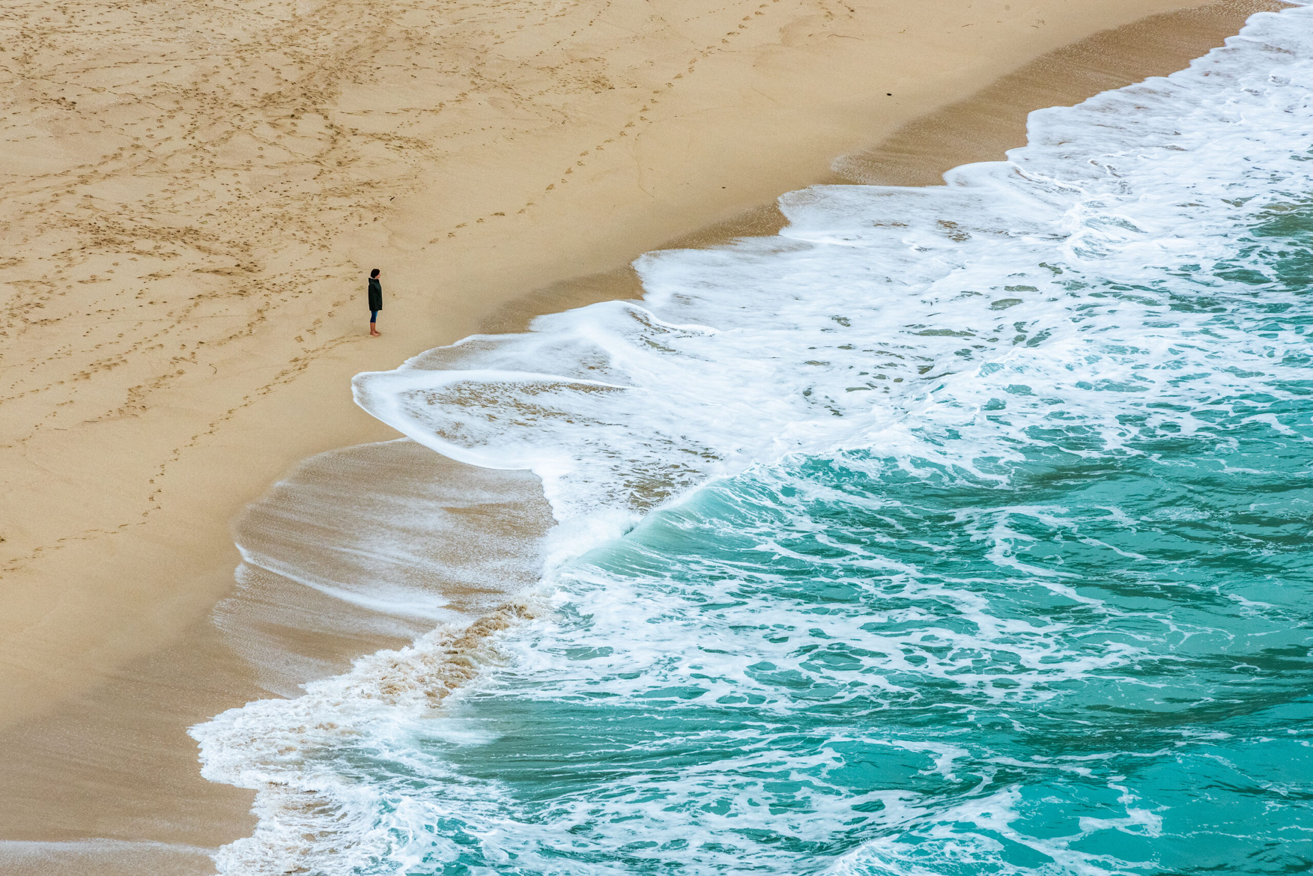 Photography of a person standing on the beach looking at the sea. Image by Jennifer Esseiva.