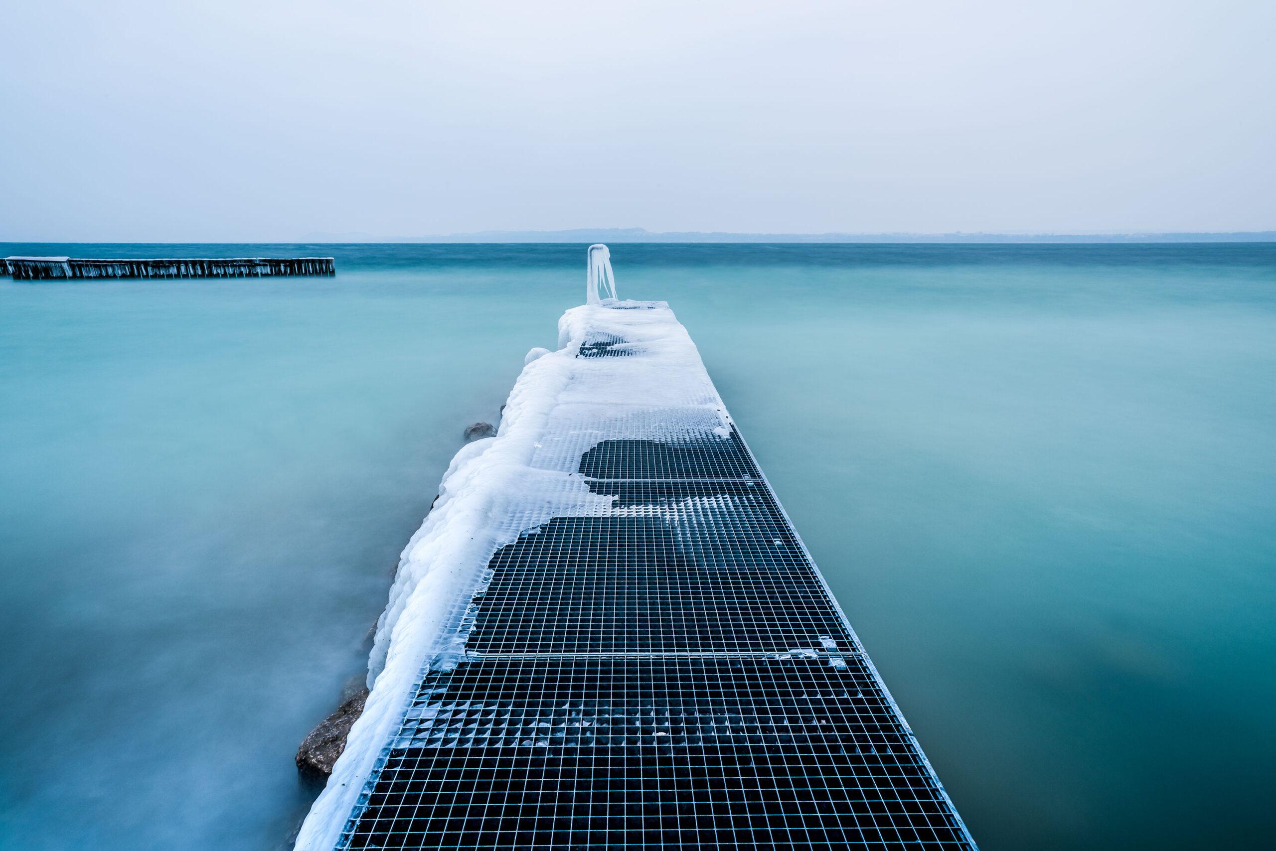 Wide-angle photography of a frozen pontoon of the Lake Neuchâtel. Image by Jennifer Esseiva.