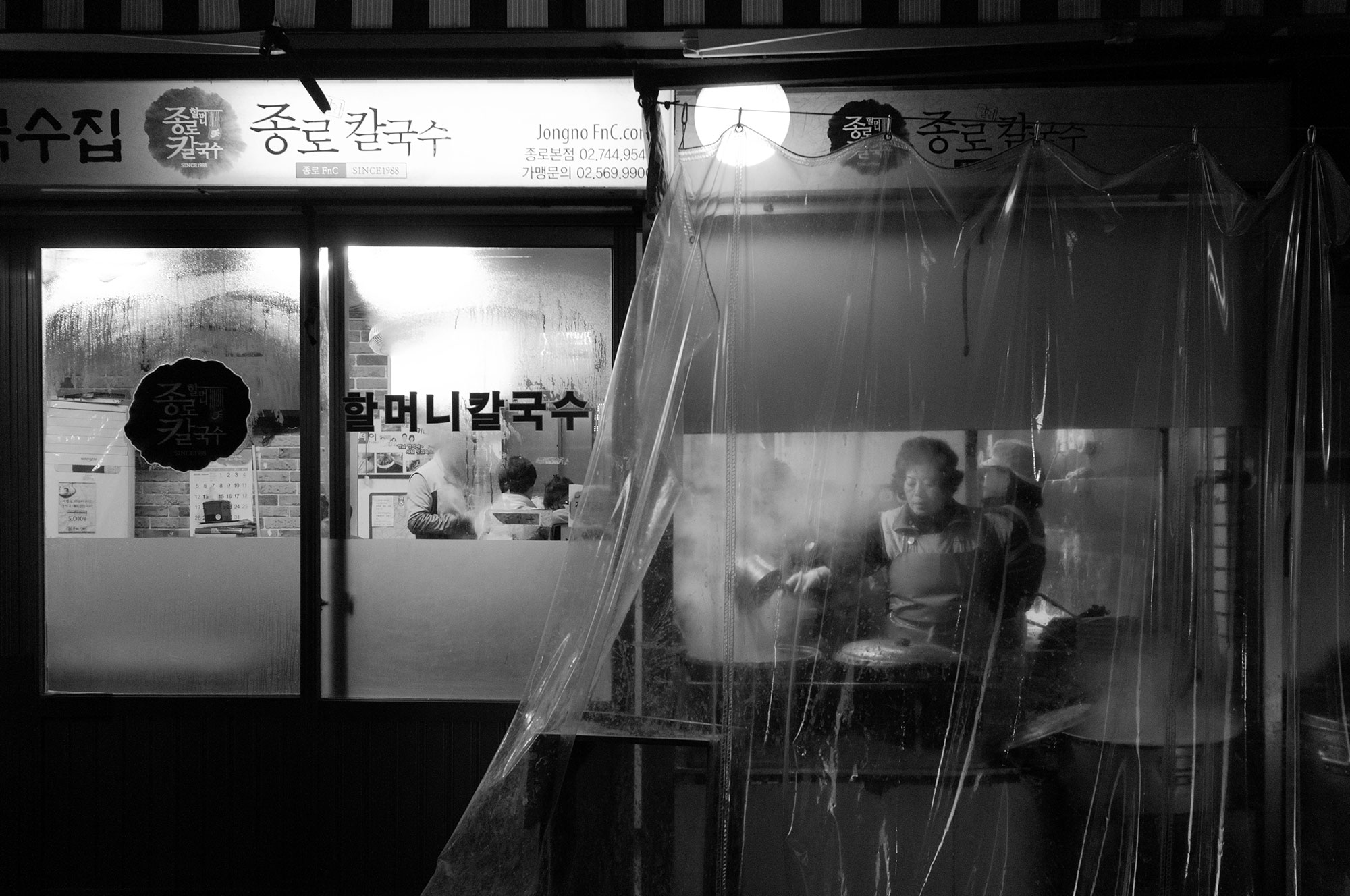 Black and white photography of the back of a restaurant in Seoul. Image by Jennifer Esseiva.