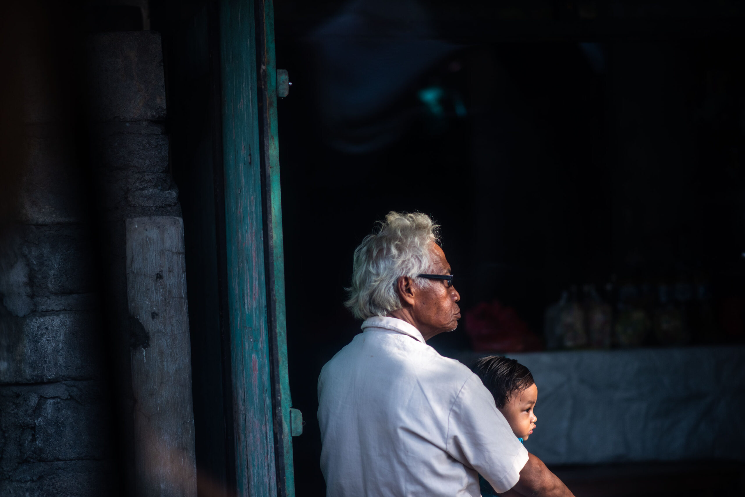 Grand pa and his grand child sit at the entrance of their home looking at the street, in Bali.